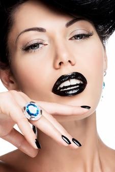 Ritratto di unghie, labbra e occhi della donna glamour dipinti di colore nero