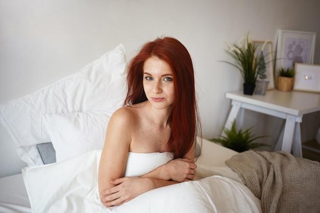 Ritratto di donna europea adulta glamour con i capelli lunghi zenzero seduta sul letto nella sua stanza, avvolta in una coperta bianca, sorridendo con gioia. riposo, relax, ora di andare a dormire e concetto di biancheria da letto