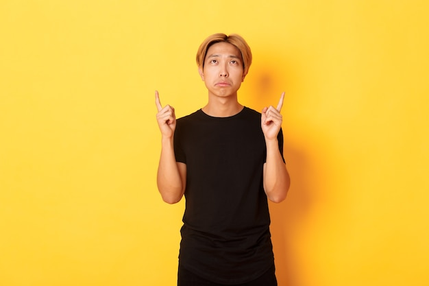 Portrait of gloomy asian blond man, wearing black t-shirt, sulking disappointed and pointing fingers up, yellow wall.