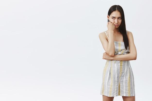Ritratto di donna asiatica carina cupa e lunatica in abito alla moda, appoggiata al pugno e guardando in basso, sconvolta