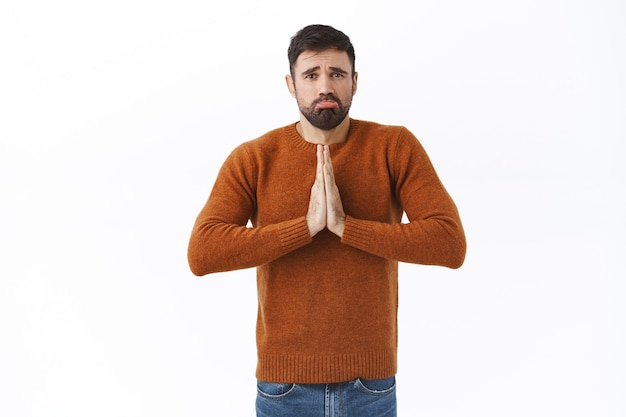 Portrait of gloomy whining young man stuck difficult situation, need lend money, clasp hands in pray, sobbing and frowning, begging for favour, need help, stand white wall
