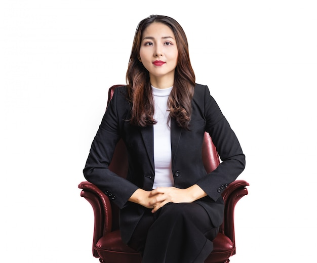 Портрет хорошего отношения личности азиатской деловой женщины, сидящей на кресле красной кожи на белой изолированной стене