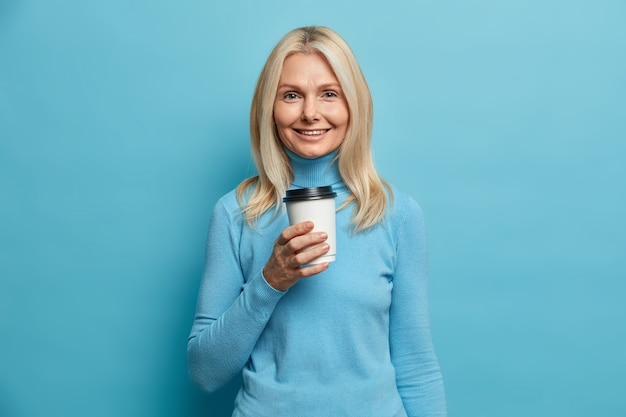 Portrait of good looking adult european woman holds disposable cup of coffee