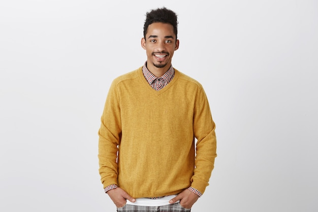 Portrait of good-looking african-american with afro hairstyle in stylish yellow pullover holding hands in pockets, smiling casually