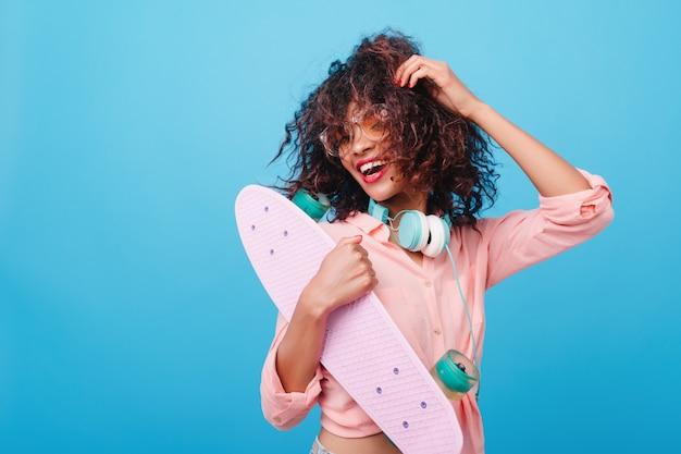 Ritratto di bello modello femminile africano in cuffie che tiene nuovo skateboard e sorridente. ridendo signora mulatta in camicia rosa alla moda che gioca con i capelli castani ricci.