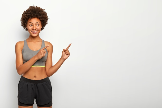 Portrait of good looking afro woman points away on blank space, smiles pleasantly, wears top and shorts, copy space against white wall