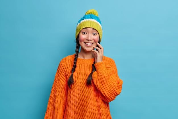 Ritratto di bella ragazza millenaria asiatica con due trecce tocca delicatamente il viso ha guance rosse dal gelo sorride ampiamente