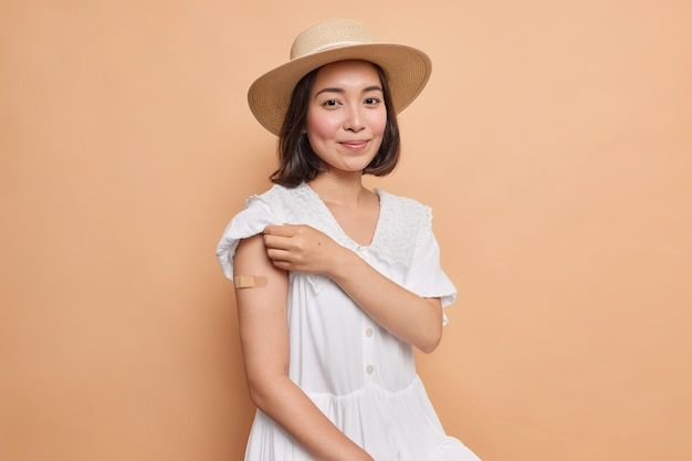 Portrait of good looking asian woman with dark hair shows arm with adhesive plaster after getting inoculation of vaccine