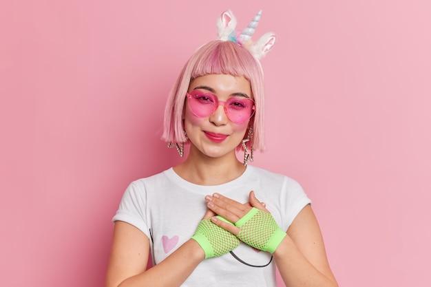 Ritratto di bella donna asiatica con acconciatura alla moda indossa occhiali da sole a forma di cuore con archetto di unicorno e maglietta fa un gesto grato