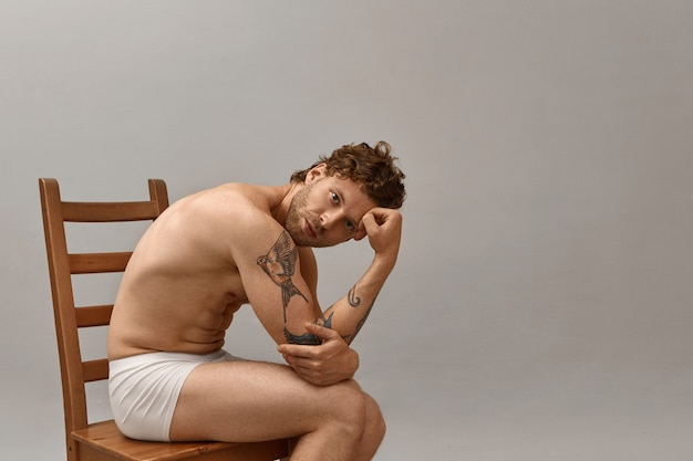 Portrait of good looking bearded naked male with tattooed arm sitting topless on wooden chair, wearing only white boxer shorts.
