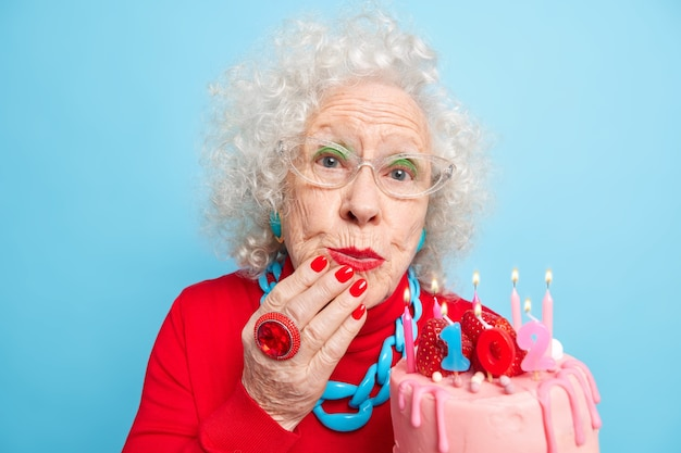 Portrait of good looking beautiful woman wears jewelry and festive red clothes holds cake with candles celebrates 102nd birthday being on party for elderly people