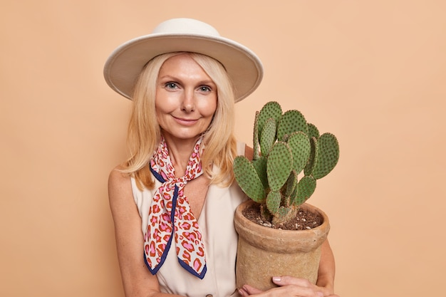 Portrait of good looking blonde woman with minimal makeup well cared comlexion holds pot of cactus wears hat dress tied kerchief isolated over beige wall
