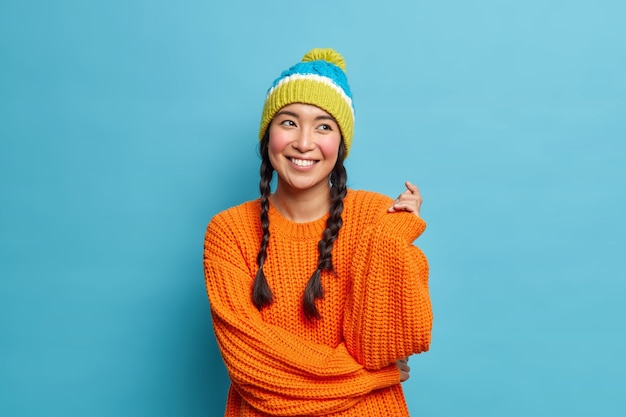 Portrait of good looking brunette asian woman with two pigtails has romantic expression dreams about something pleasant dressed in winter clothes isolated over blue wall