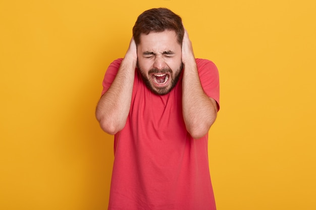 Portrait of good looking caucasian guy in red t shirt, male yelling with closed eyes and covering ears palms, not want to hear noise