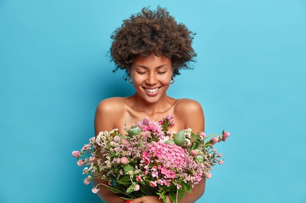 Portrait of good looking cheerful curly haired afro american woman poses with bare shoulders gets present from beloved person enjoys spring time has happy mood isolated over blue studio wall
