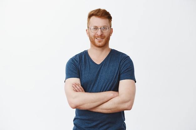Ritratto di un bel ragazzo maturo dai capelli rossi fiducioso con setole in occhiali rotondi, tenendo le mani sul petto e sorridendo ampiamente