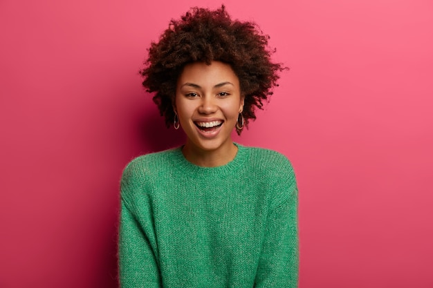 Portrait of good looking curly ethnic woman smiles broadly, enjoys day off, has happy talk with interlocutor, discusses holiday preparation, wears green sweater, isolated on pink wall.