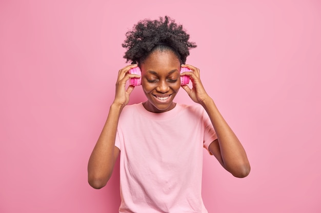 Portrait of good looking curly haired young afro american woman keeps hands on wireless headphones