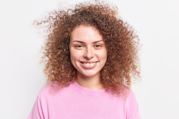 Il ritratto di bella donna riccia sorride a trentadue denti felice di sentire buone notizie trascorre il tempo libero con gli amici vestiti con un maglione casual isolato sul muro bianco. concetto di persone ed emozioni