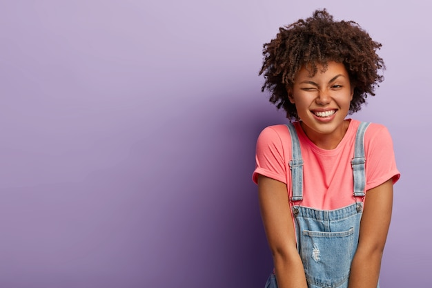 Portrait of good looking dark skinned woman with curly hairdo, blinks eye, has fun, smiles pleasantly, dressed in stylish clothes, expresses happy emotions, isolated over purple background, copy space