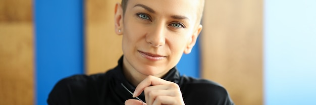 Portrait of good-looking female holding stylish silver accessory. short haired young woman in black top.