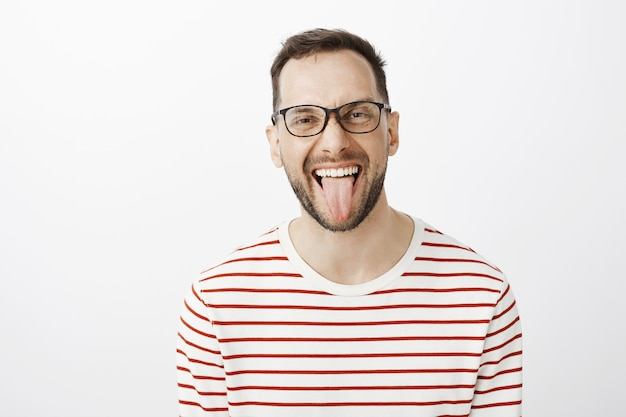 Portrait of good-looking funny adult coworker in black glasses, sticking out tongue and smiling joyfully, being carefree and careless about rules or duties
