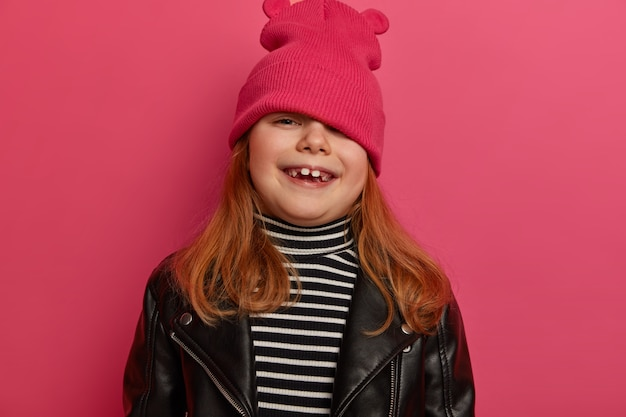 Portrait of good looking girl looks from under hat, plays hide and seek, smiles broadly, has upbeat mood, dressed in fashionable clothes, has happy childhood, went shopping with mom at weekend