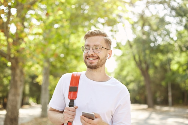 Portrait of good looking happy male with mobile in hand, looking away and smiling broadly, wearing white t-shirt and red backpack, walking through park on bright and warm day