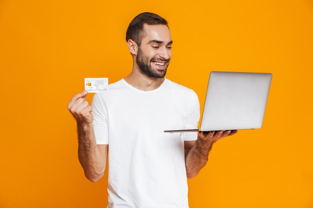 Portrait of good-looking man 30s in white t-shirt holding silver laptop and credit card, isolated