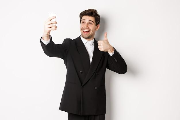 Ritratto di bell'uomo che si fa selfie alla festa di capodanno, indossa un abito, scatta foto su smartphone e mostra pollice in su, in piedi su sfondo bianco.