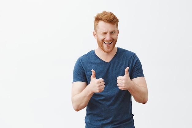 Portrait of good-looking man with ginger hair showing thumbs up and winking with hint, liking and supporting great decision, cheering over gray wall
