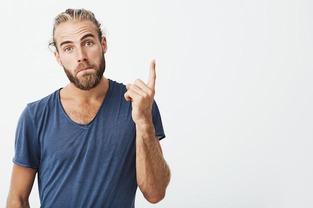 Ritratto di bel ragazzo virile con acconciatura alla moda e barba rivolta verso l'alto