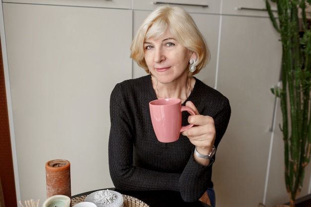 Portrait of good looking mature healthy slim woman with cup of coffee posing in her modern kitchen