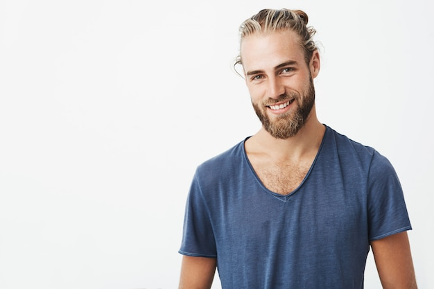 Portrait of good-looking nordic unshaven man with fashionable hairdo posing