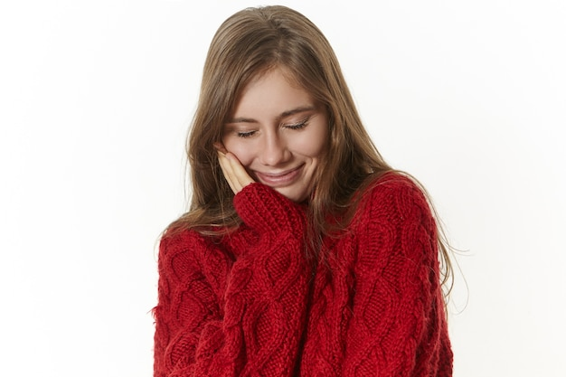 Portrait of good looking positive young caucasian female with pleased friendly smile, keeping eyes closed, dreaming, touching cheek, wearing fashionable warm maroon pullover on cold winter day
