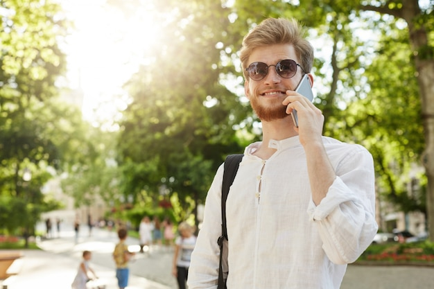 Portrait of good looking red haired man in white shirt and sunglasses smiling, talking on phone on the way on work meeting in cafeteria.