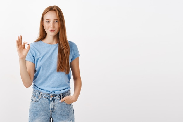Portrait of good-looking satisfied and happy redhead woman in blue t-shirt holding hand in pocket showing okay or perfect gesture with fingers smiling liking or accepting plan