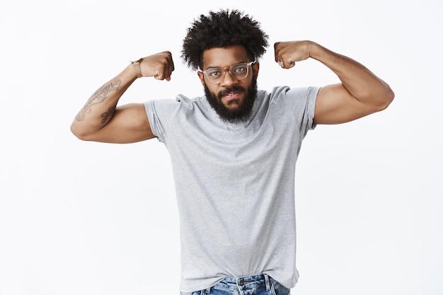 Ritratto di bel ragazzo afroamericano soddisfatto di sé che si allena per essere forte e mascolino sfoggiando bicipiti con le mani alzate che sembrano seri e impegnativi davanti come invitanti in palestra