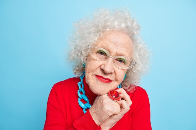 Portrait of good looking senior woman wears spectacles big ring bright makeup looks, with pleased expression dressed in red jumper