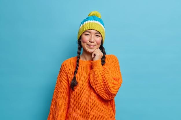 Ritratto di bella donna asiatica bruna timida con due trecce indossa maglione lavorato a maglia e cappello ha espressione faccia soddisfatta pone in studio contro passeggiate muro blu durante il periodo invernale