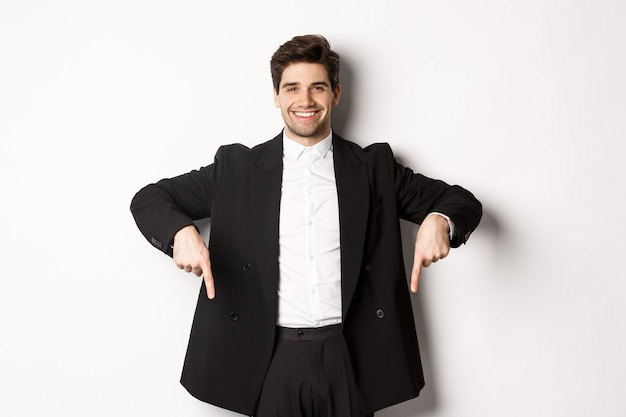 Portrait of good-looking stylish man in black suit, pointing fingers down and smiling, showing winter holidays promo, standing over white background.