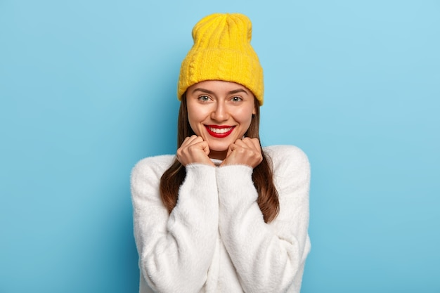 Portrait of good looking woman looks positively, smiles with pleasure, wears red lipstick, has dark hair, yellow hat, white sweater