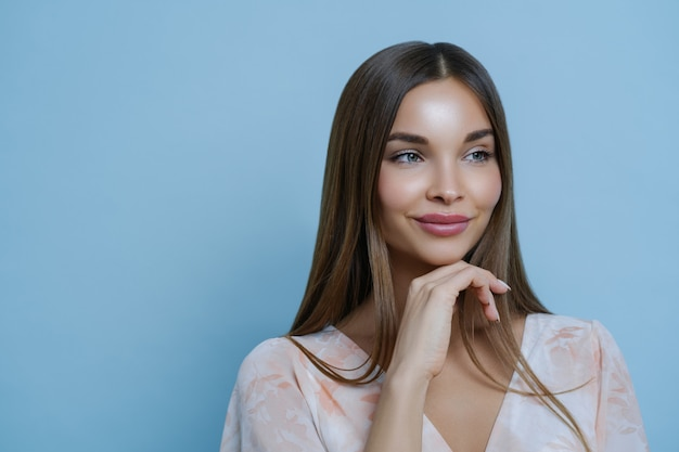 Portrait of good looking woman touches chin and has thoughtful expression