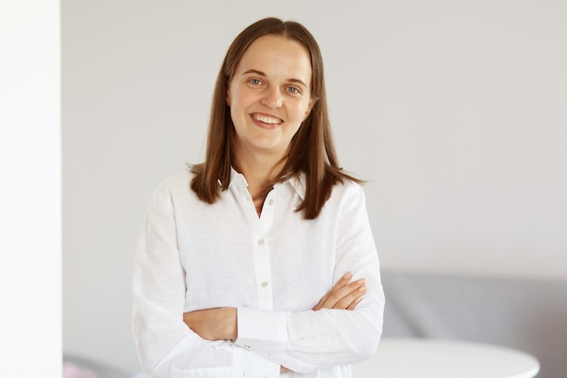 Portrait of good looking young adult woman wearing white casual style shirt, standing indoor with crossed arms, expressing positive emotions and happiness.