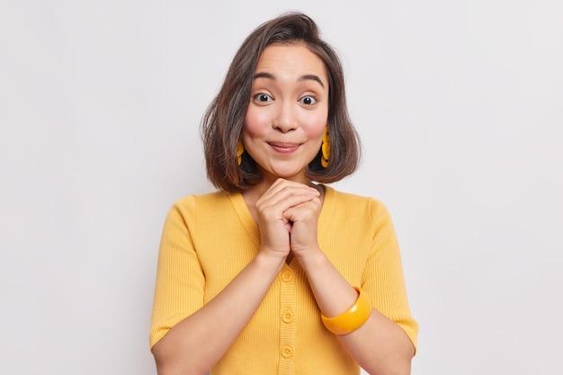 Il ritratto di giovane donna asiatica di bell'aspetto con i capelli dak naturali la pelle sana tiene le mani unite sotto il mento indossa orecchini gialli maglione e braccialetto sul braccio isolato sul muro bianco