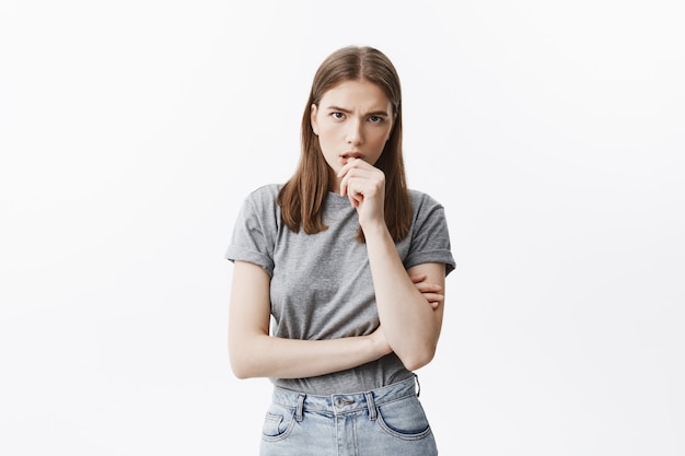 Portrait of good-looking young student girl with medium hair length and dark hair in trendy grey clothes gnaws nails on hand,  with worried expression. waiting friend from work interview