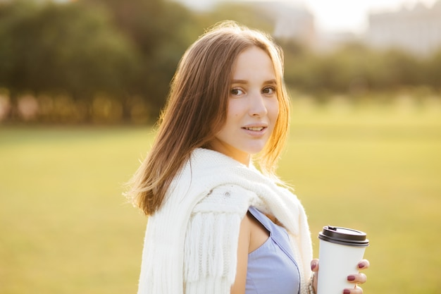 Portrait of good looking young woman with appealing look, enjoys aromatic coffee from disposable cup