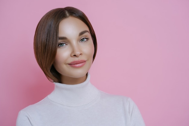 Portrait of good looking young woman with dark hair, minimal makeup, wears casual white turtleneck