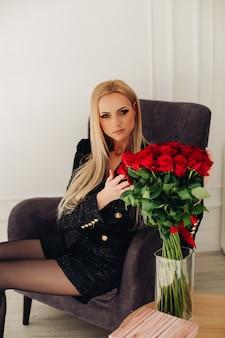 Ritratto di splendida donna bionda caucasica in pantaloncini neri e giacca toccando le rose rosse in vaso mentre era seduto in poltrona grigio scuro.