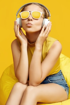 Portrait of gorgeous blonde hipster girl wearing sunglasses sitting in a sack bag with headphones on colorful yellow background